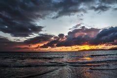 Oranje en zwarte zonsondergang bij het strand stock foto