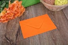 Oranje envelop en rozen op een houten achtergrond Royalty-vrije Stock Afbeelding