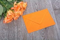 Oranje envelop en rozen op een houten achtergrond Stock Fotografie