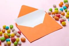Oranje envelop met een spatie voor tekst en het kleurrijke hijgen op een heldere in roze achtergrond royalty-vrije stock foto