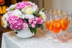 Oranje exotische die cocktail bij de lijst met een boeket van flo wordt gediend Stock Fotografie