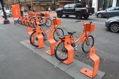 Oranje fietsen voor huur en verkeer in Portland, Oregon stock foto's