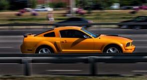 Oranje Ford Mustang GT in stad Stock Fotografie