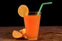 Oranje fruktsaft på svart bakgrund royaltyfria bilder