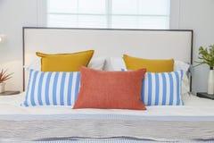 Oranje, gele en blauwe hoofdkussens op wit bed thuis stock foto