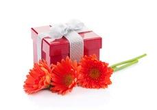 Oranje gerberabloemen en rode giftdoos Stock Fotografie