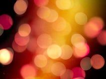 Oranje gloed op een donkere nachtachtergrond met het gloeien rood vaag om lichten royalty-vrije stock afbeelding