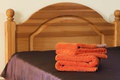 Oranje handdoeken op het violette behandelde bed Royalty-vrije Stock Fotografie