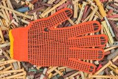 Oranje handschoenen die op de achtergrond van de pennen liggen stock afbeeldingen