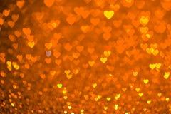 Oranje hart bokeh achtergrond De textuur van de valentijnskaartendag stock afbeelding