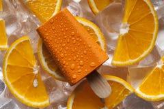 Oranje ijslollie en vruchten op ijsblokjes stock afbeeldingen