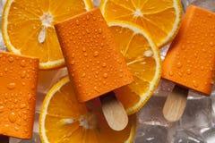 Oranje ijslollie op ijs en vruchten royalty-vrije stock foto's