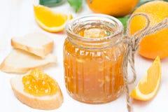 Oranje jam in een glaskruik en een vers brood Royalty-vrije Stock Fotografie
