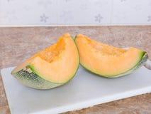 Oranje Japanse meloen op een wit blok in keuken Stock Foto