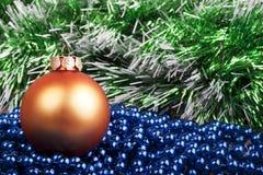 Oranje Kerstmisbal en blauwe parels op een achtergrond van groen GA Stock Fotografie