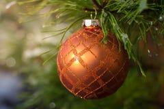Oranje Kerstmisbal op ijzige altijdgroene bladeren Stock Afbeelding