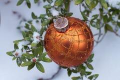 Oranje Kerstmisbal op installatie met verse sneeuw Stock Fotografie