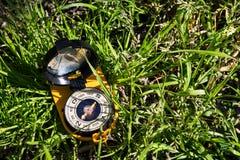 Oranje kompas in het gras op een zonnige dag Richtlijn en reisconcept stock foto's