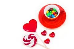 Oranje kop met kleurrijke knoop-vormige chocolade en lollys Royalty-vrije Stock Foto's