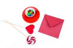Oranje kop met kleurrijke knoop-vormige chocolade, rode envelop en lollys Stock Afbeeldingen