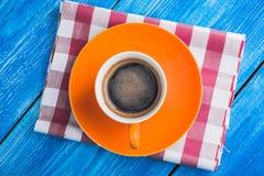 Oranje kop van koffie met servet Stock Fotografie