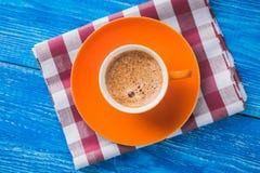 Oranje kop van koffie met servet Stock Foto's