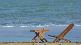 Oranje kop van koffie op bruine houten lijst aangaande strand stock video