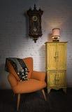 Oranje leunstoel, gele kast, slingerklok en verlichte schemerlamp Royalty-vrije Stock Afbeelding