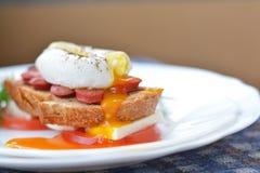 Oranje, lopende dooier van gestroopt ei op worst, brood, feta chesse, tomaat dicht omhoog Stock Afbeelding
