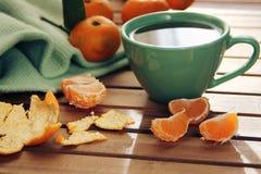 Oranje mandarijn en mandarin plakken, groene kop thee Royalty-vrije Stock Afbeelding