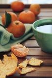 Oranje mandarijn en mandarin plakken, groene kop thee Royalty-vrije Stock Foto's