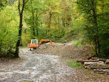 Oranje mechanische graver in bos Stock Afbeeldingen