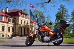 Oranje motorfiets voor het huis klaar te gaan - de lente zonnige dag stock foto's