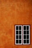 Oranje muur en venster Stock Afbeeldingen