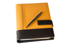 Oranje notitieboekjeagenda en pen Stock Fotografie
