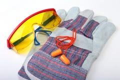 Oranje oordopje, bouwvakker, veiligheidsbril, handschoenen Oordopje om lawaai op een witte achtergrond te verminderen u kunt uw p stock afbeeldingen
