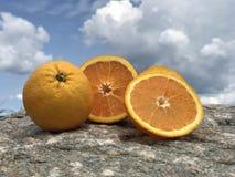 Oranje organisch fruit een heahty sappig vitamine Cfruit in de aard op een steen met een blauwe hemel en wolken Stock Foto's