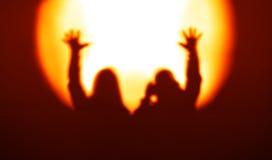Oranje paarsilhouetten met handen omhoog gezien schijnwerper B Royalty-vrije Stock Fotografie