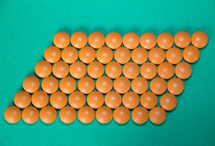 Oranje pillen op groen Stock Afbeelding