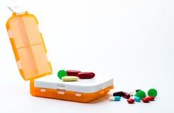 Oranje pillenvakje met kleurrijke die capsulepillen op witte achtergrond met exemplaarruimte worden geïsoleerd Royalty-vrije Stock Fotografie
