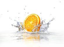 Oranje plak die en in duidelijk water valt bespat. royalty-vrije stock afbeeldingen