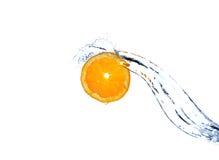 Oranje plak die en in water vallen bespatten. stock afbeeldingen