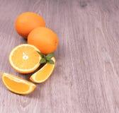 Oranje plakken naast gehele citrusvrucht versierde munt op een houten oppervlakte stock afbeelding