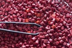 Oranje plastic korrels met pincet Stock Foto's