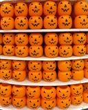 Oranje plastic pompoenemmers op een opslagplank Royalty-vrije Stock Foto's