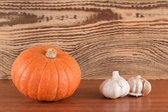 Oranje pompoen en knoflook op een houten lijst Stock Afbeelding