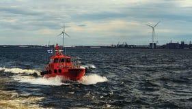 Oranje proefboot die voor medewerker aan vrachtschip volgen Loodsen van schip stock foto's