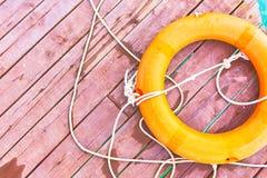 Oranje reddingsboei met kabel op een houten pijler dichtbij overzees stock afbeelding