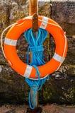Oranje reddingsboei op een redding van de steenmuur, blauwe kabel, oceaankust Stock Foto's