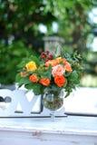 Oranje Rozen in Duidelijke Glasvaas op Witte Lijst met Vage Groene Tuinachtergrond Bloemenregeling De lente of stock foto's